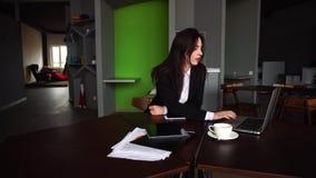 Stående av den härliga kvinnliga sekreteraren som poserar och ser bort, medan arbeta på datoren, och sitter på tabellen med arkivfilmer
