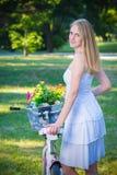 Stående av den härliga kvinnlign med cykeln i en parkera royaltyfri bild