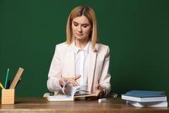 Stående av den härliga läraren som sitter på tabellen arkivbild