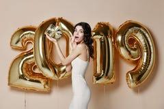 Stående av den härliga le flickan i skinande guld- klänning som kastar konfettier och att ha gyckel med guld- 2019 ballonger på b royaltyfria foton