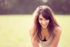 Stående av den härliga le flickan med långt svart hår i gardenlen som ler flickan med långt svart hår i ängen Arkivbilder