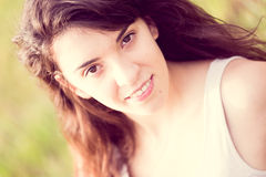 Stående av den härliga le flickan med långt svart hår i gardenlen som ler flickan med långt svart hår i ängen royaltyfria foton