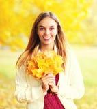 Stående av den härliga le kvinnan med gula lönnblad i solig höstdag arkivbilder