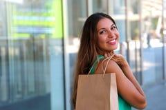 Stående av den härliga le kvinnan med shoppingpåsen på väggexponeringsglasbakgrund utomhus kopiera avstånd arkivbild