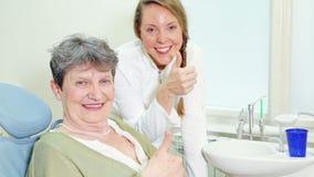 Stående av den härliga le tandläkaren och åldringkvinnan som ger upp tummar arkivfilmer
