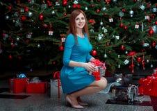 Stående av den härliga le unga kvinnan och att stå nära julgranen som rymmer gåvan royaltyfria bilder