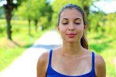 Stående av den härliga le unga kvinnan som tycker om yoga och att koppla av och att känna sig vid liv och att andas ny luft som f royaltyfria bilder