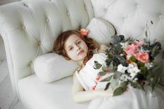 Stående av den härliga lilla flickan i den vita klänningen på den vita soffan arkivfoto