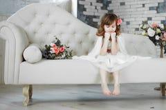Stående av den härliga lilla flickan i den vita klänningen på den vita soffan arkivfoton