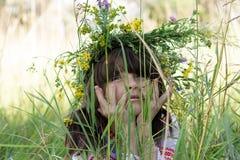 Stående av den härliga lilla flickan med en färgrik garlang på hennes huvud och händer under hennes haka i högt grönt gräs på en  Royaltyfri Foto