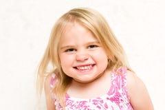 Stående av den härliga litet barnflickan som Cheekily grinar arkivbilder