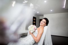 St?ende av den h?rliga lyckliga bruden som sitter p? soffan arkivbilder