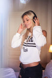 Stående av den härliga lyckliga flickan med hörlurar som lyssnar till popmusik Arkivbild