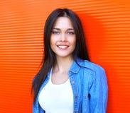 Stående av den härliga lyckliga le brunettkvinnan i jeans Royaltyfri Fotografi