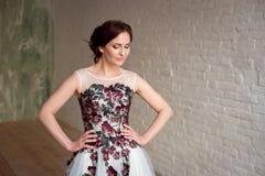 Stående av den härliga lyxiga kvinnliga modellen med medelbrunthår i ett långt fashinable klänninganseende i rummet arkivfoton