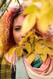 Stående av den härliga mörkhyade flickan med rött hår och guld- kanter arkivfoto