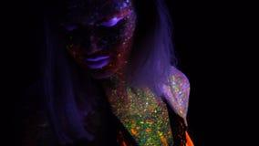 Stående av den härliga modekvinnan i UV ljus för neon Modell Girl med fluorescerande idérik psykedelisk makeup, konst arkivfilmer