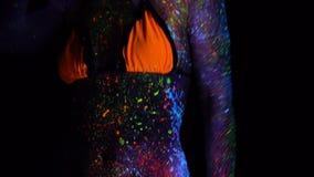 Stående av den härliga modekvinnan i UV ljus för neon Modell Girl med fluorescerande idérik psykedelisk makeup, konst lager videofilmer
