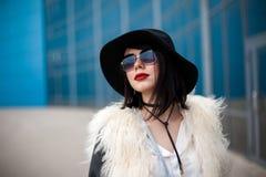 Stående av den härliga modellen i pälslag, hatt och solglasögon Urb Royaltyfria Bilder