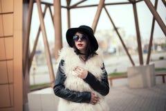 Stående av den härliga modellen i pälslag, hatt och solglasögon Urb Royaltyfri Foto