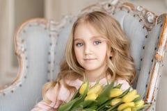 Stående av den härliga nätta flickan med gula blommatulpan som sitter i fåtölj som ler Inomhus foto härlig tulpan för makrofjäder fotografering för bildbyråer