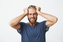 Stående av den härliga nordiska grabben med moderiktig frisyr och huvudet för skägg hållande med händer som lider från huvudvärk  Royaltyfri Bild
