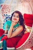 stående av den härliga orientaliska kvinnan i traditionell klänning som kopplar av på soffan Arkivfoton