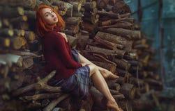 Stående av den härliga redhaired flickan I i en varm tröjasitti royaltyfria bilder
