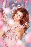 Stående av den härliga romantiska flickan bland orientaliska trädfruncher för körsbärsröd blomning i vårträdgård Arkivfoton