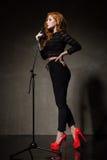 Stående av den härliga sångaren i röda häl och svartkläder Royaltyfri Fotografi