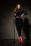 Stående av den härliga sångaren i röda häl och svartkläder Royaltyfri Bild
