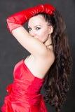 Stående av den härliga sexiga brunettkvinnan med långt hår i röd satängklänning Arkivbild