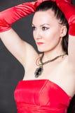 Stående av den härliga sexiga brunettkvinnan med långt hår i röd satängklänning Royaltyfri Foto