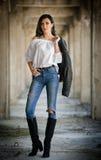 Stående av den härliga sexiga unga kvinnan med den moderna dräkten, läderomslaget, jeans, den vita blusen och svartkängor Arkivfoto