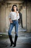 Stående av den härliga sexiga unga kvinnan med den moderna dräkten, läderomslaget, jeans, den vita blusen och svartkängor Arkivbilder