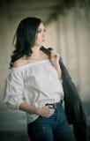 Stående av den härliga sexiga unga kvinnan med den moderna dräkten, läderomslaget, jeans, den vita blusen och svartkängor Royaltyfri Bild