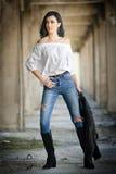 Stående av den härliga sexiga unga kvinnan med den moderna dräkten, läderomslaget, jeans, den vita blusen och svartkängor Royaltyfria Bilder