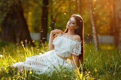 Stående av den härliga sinnliga brunettflickan i den vita klänningsittien Arkivfoto