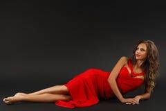 Stående av den härliga sinnliga kvinnan i röd klänning för mode Arkivbilder