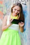 Stående av den härliga stilfulla blonda unga kvinnan som använder minnestavlaPCdatoren som har roligt lyckligt le Arkivbilder