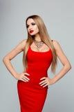 Stående av den härliga trendiga kvinnan i en ljus röd klänning med en guld- halsband och röda kanter Spenslig flicka med royaltyfri bild
