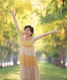 Stående av den härliga unga asiatiska kvinnan som fritt känner sig med relaxi Arkivbild