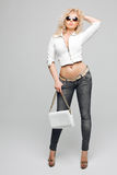 Stående av den härliga unga blonda kvinnan med lockigt hår Flickan bar ett omslag för vitt läder, jeans och royaltyfria foton
