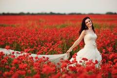 Stående av den härliga unga bruden i fält mycket av röda vallmo Royaltyfri Fotografi