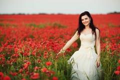 Stående av den härliga unga bruden i fält mycket av röda vallmo Arkivbild