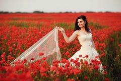 Stående av den härliga unga bruden i fält mycket av röda vallmo Arkivfoton