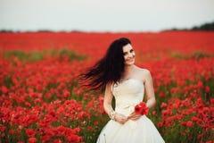 Stående av den härliga unga bruden i fält mycket av röda vallmo Arkivfoto
