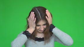 Stående av den härliga unga brunetten som trycker på hennes tempel som känner spänning, på grön bakgrund lager videofilmer