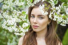 Stående av den härliga unga brunettkvinnan i vårblomning Fotografering för Bildbyråer