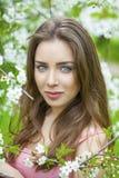 Stående av den härliga unga brunettkvinnan i vårblomning Arkivfoto